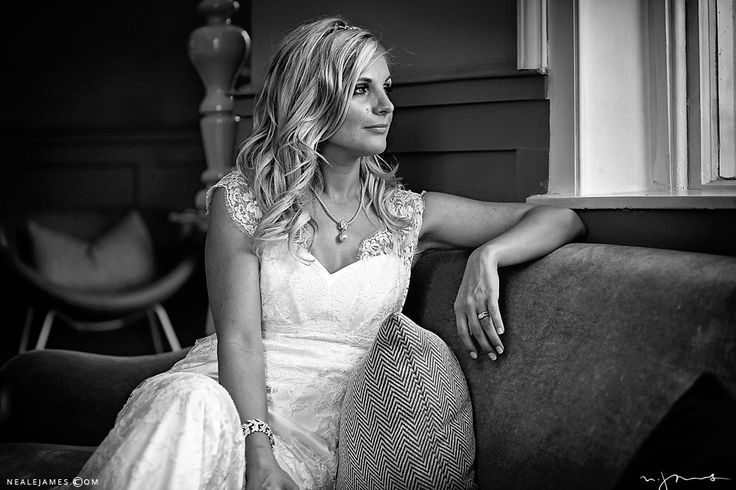 Window lit black and white image of a bride at Stoke Place