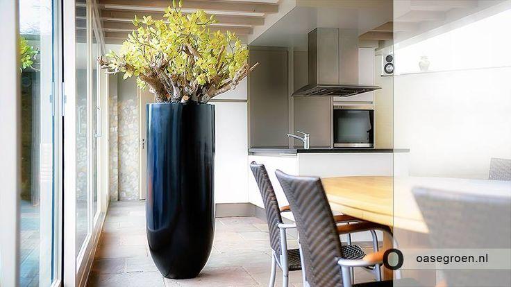 Hoogglans zwarte vaas gecombineerd met fris groene kunstbloemen. Een zonnige beleving voor in de huiskamer.