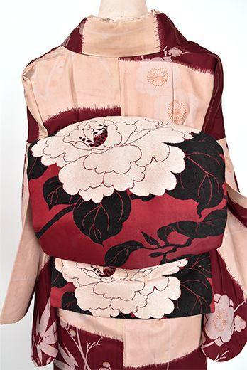 ガーネットのようなほのかに紫がかった深く美しいルージュレッドの地に、大輪の牡丹の花が織りだされた大正ロマン・昭和レトロな詩情ただよう名古屋帯です。