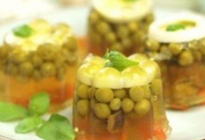włoszczyzna 1 cebula jajko ugotowane na twardo groszek zielony grzybki, korniszony 3 łyżki żelatyny 2 kulki ziela angielskiego sól 1 łyżeczka ziarenek pieprzu  Warzywa zalewam wodą (ok. 1-1,3 litra), doprawiam pieprzem, solą i zielem angielskim i gotuję do miękkości. Ostudzony wywar oddzielam od warzyw i mieszam z żelatyną rozpuszczoną w ok. 1/3 szklanki wrzątki, a z warzyw kroję marchewkę w plastry.Do kokilek wkładam plasterki jajek, na to groszek, grzybki, korniszony i march...