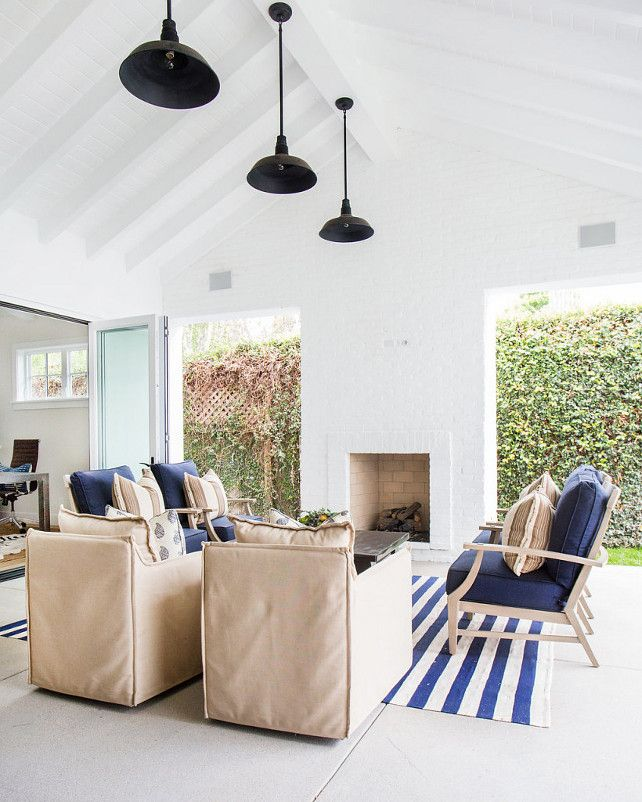 This covered patio with vaulted ceiling features white wood beams and black vintage barn pendants. Natural linen chairs faces an outdoor white brick fireplace flanked by open doorways across from a reclaimed wood coffee table and blue chairs. A blue striped rug adds a coastal feel to the space.