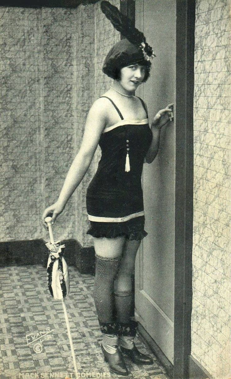 ARCADE CARD - MACK SENNETT COMEDIES - WOMAN IN BATHING SUIT AND FEATHERED BONNET STANDING BY DOOR