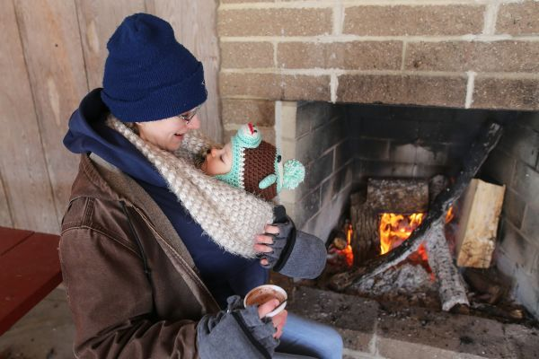 Danielle Hodges and her eleven month-old baby Phebe sit next to a fire after taking a walk in Kendrick woods on Saturday morning.  Amanda Wilson -The Lima News