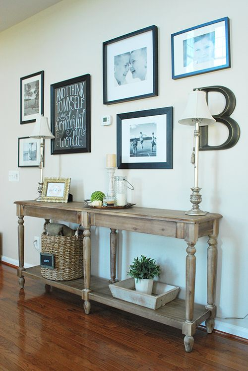 Create a gallery wall ouf of that boring spot in the hallway or beneath the stairs!  A long console table holds picture frames, candles, a matched pair of lamps, a topiary, a basket full of warm throws, and seasonal decor.  On the wall, the black frames provide a cohesive look--even though they're different styles--and the B monogram is a fun personalized touch.  Sponsored by HomeGoods Happy by Design.