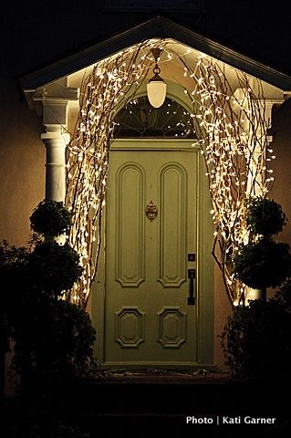 wrapping branches in lights on the front porch for holiday decor. Simple with a huge impact!