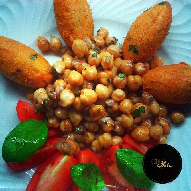 Bolinhos de bacalhau com grão de bico e salada de tomate. Codfish cakes with chickpeas and tomato salad . Typical portuguese dish. Prato típico português.