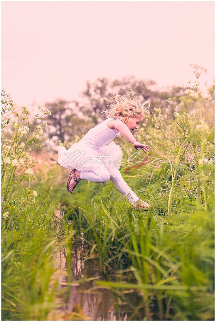 kinderfotografie buiten, springend over sloot met modder en nette jurkjes