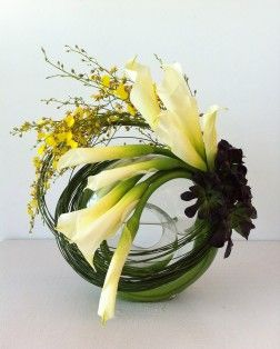 White calla lillies, black succulent accents, yellow orchids, and long grasses in