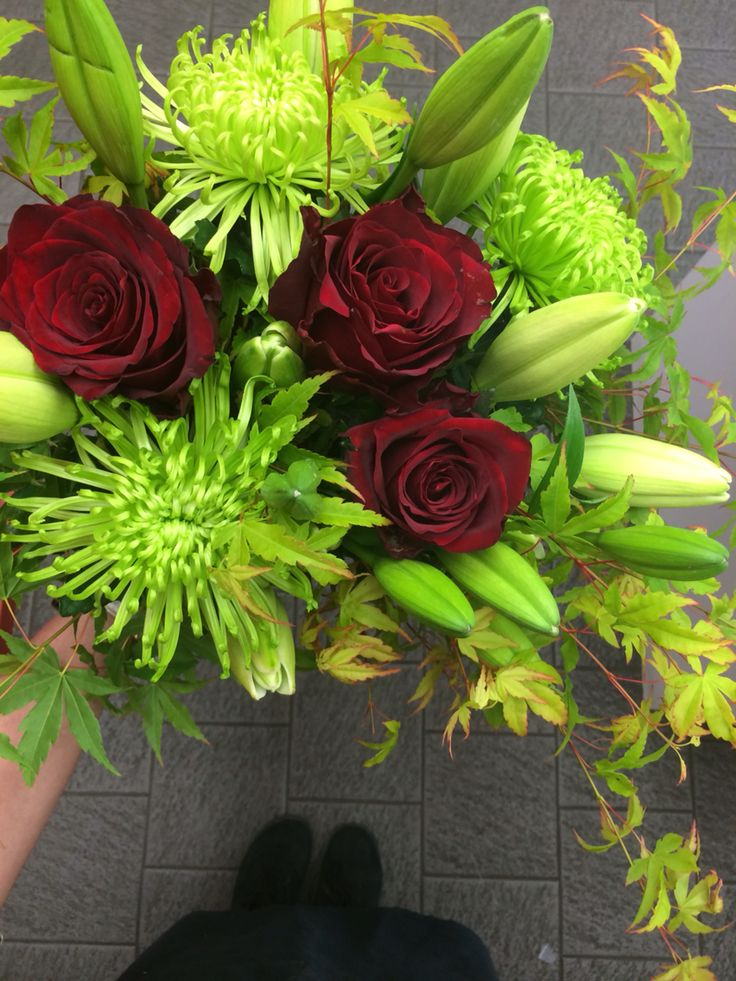 Green disbuds, white asiatic lillies, red roses and maple greenery