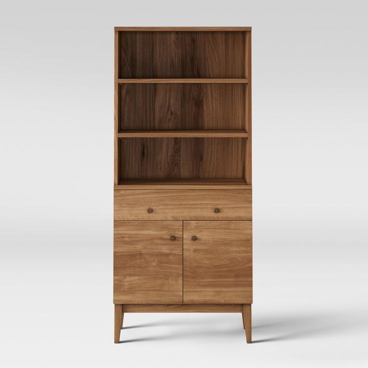 With the Siegel Bookcase with Doors from Project 62™, you'll have a place to display books and stow away other items you don't use on a frequent basis. This tall bookcase features a durable wood construction with a light walnut finish, along with tapered legs to give off a modern look. Use the three shelves to showcase things like books and potted plants, then conceal items you don't want on display in the drawer or bottom compartment. You'll love placing it alongside...