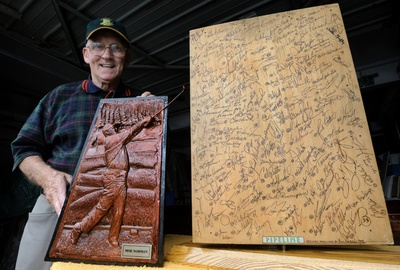 Bill Herron displays the cast of a carving (which is on the front of the block of famous golfer's signatures on the right) he had commissioned of Moe Norman, at his home in Kitchener.