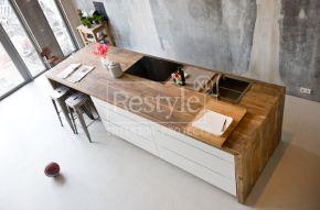 Witte keuken met houten blad op betonvloer.