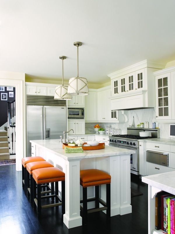 love the orange stools in a white kitchen.