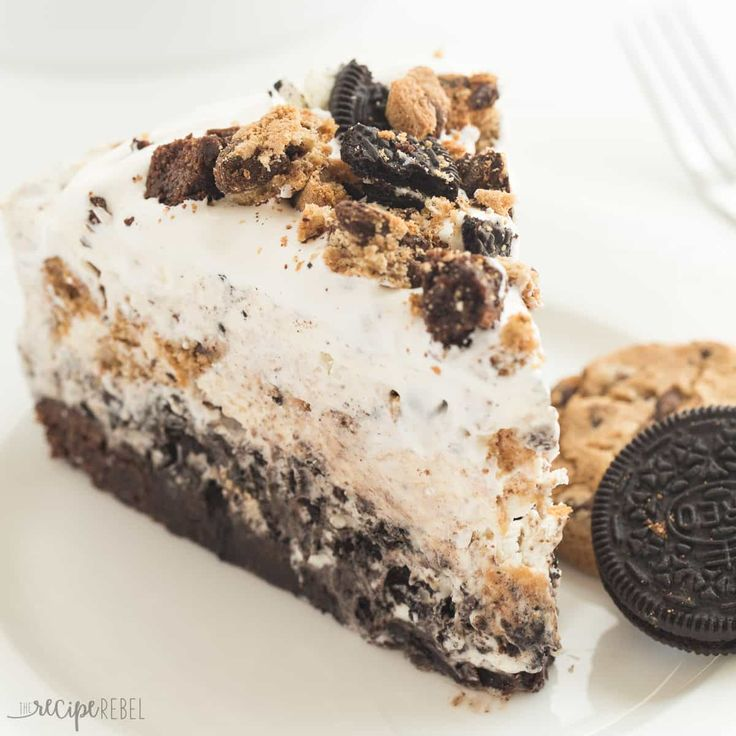 The ULTIMATE Ice Cream Cake! A brownie base topped with a no churn Oreo ice cream layer, fudge crumbles, a Chocolate Chip Cookie ice cream layer, then covered in whipped cream!