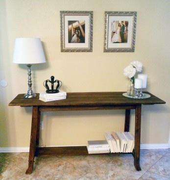 Entryway makeover with a rustic table, silver accents, and a white book collection.  Paint color: Behr Raffia Cream