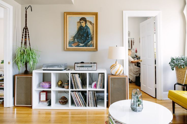 Another Rhode Island Antique Mall find, the blue lady portrait watches over the couple's record collection and hand-me-down record player. . More macrame hanging above a vintage Pioneer speaker. The shelving unit is from IKEA.