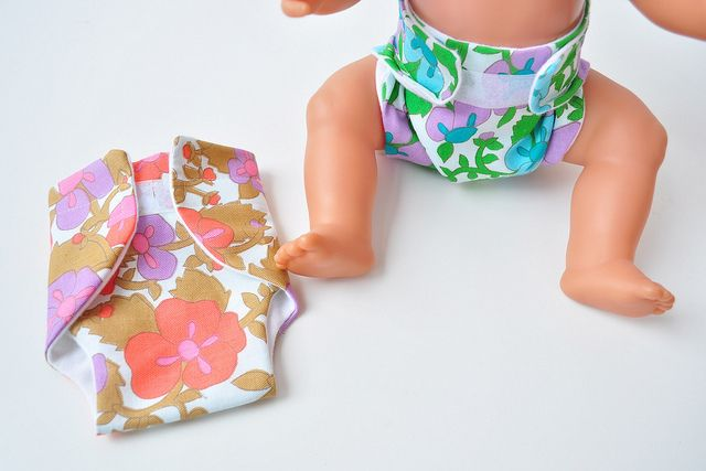 Doll pampers (site is in Dutch but instructions are easy to understand if you follow the photo's) just make sure to make a paper template first to see if it fits!