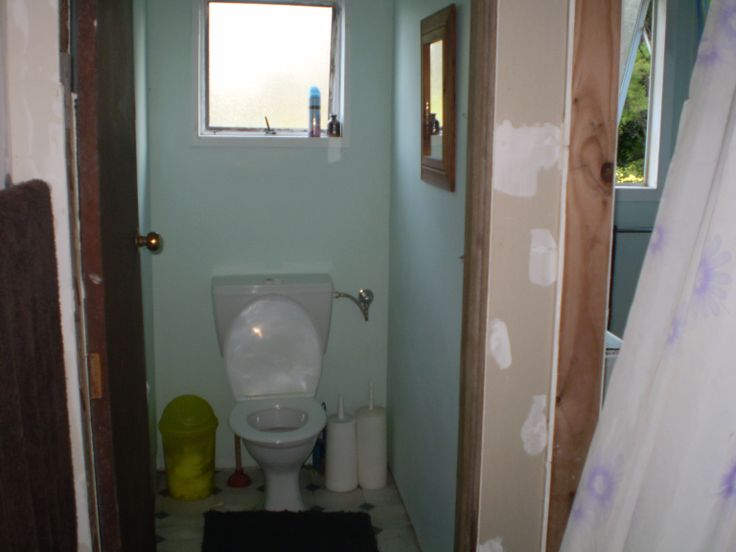 The old toilet with damp concrete floor and something that was trying to be a door!! Bathroom door, or should I say curtain flapping in the breeze to the right!
