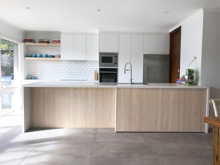 Modern Kitchen completed in Beaumaris. Dulux lexicon satin 2-Pac painted cabinetry with feature Polytec Nordic oak woodmatt island back and floating shelves. Finished with Caesar stone calacutta Nuvo stone benchtops.