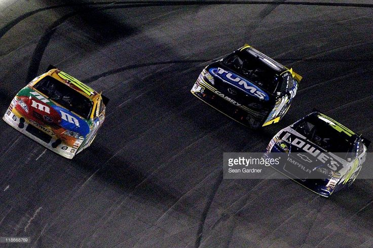 Kyle Busch, driver of the #18 M&M's Toyota, leads David Reutimann, driver of the #00 Tums Toyota, and Jimmie Johnson, driver of the #48 Lowe's Chevrolet, during the NASCAR Sprint Cup Series Quaker State 400 at Kentucky Speedway on July 9, 2011 in Sparta, Kentucky.