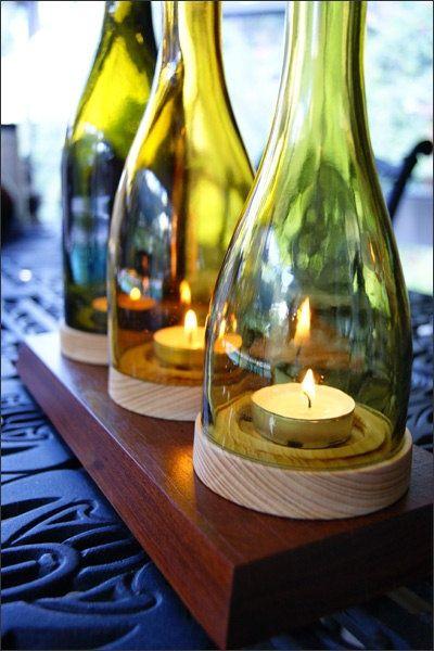 Aqui a base da garrafa também foi cortada e um pedaço de madeira deixa o porta-velas ainda mais romântico. / Crédito: Pinterest.