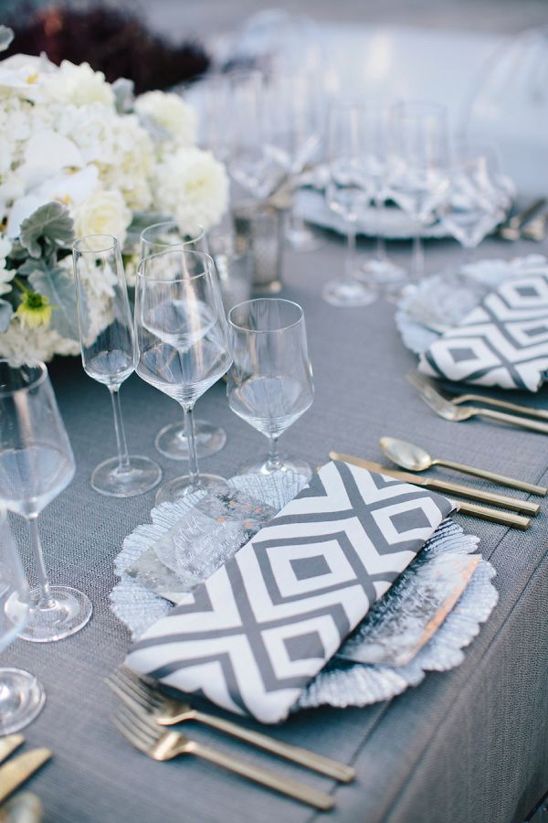 Grey and white patterned napkins, custom linens and metal menu: http://www.stylemepretty.com/2016/09/30/gorgeous-gray-modern-waterfront-wedding/ Photography: Millie Holloman - http://www.millieholloman.com/