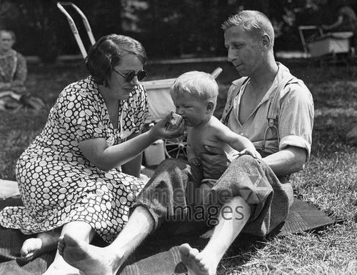Familie, ca. 1935 Timeline Classics/Timeline Images #Familie #vater #Mutter #Kind #füttern #Sonne #Sommer #Freizeit #1930er #1930ies #family