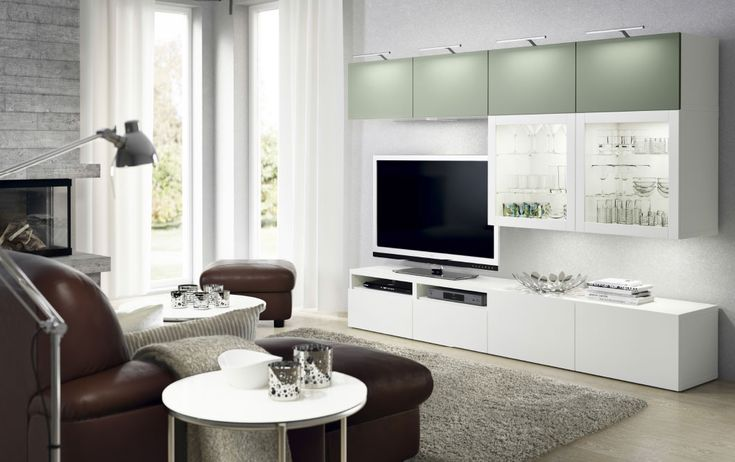 A living room with a white TV bench with white drawers and wall cabinets with a mix of light green doors and white doors with tempered glass panels. Shown together with a dark brown two-seat leather sofa with chaise lounge and a footstool.