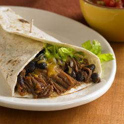 Southwest Beef and Bean Burritos : Slow cooked shredded beef and black beans in a flavorful sauce rolled up in flour tortillas with cheese and lettuce make these burritos burst with flavor
