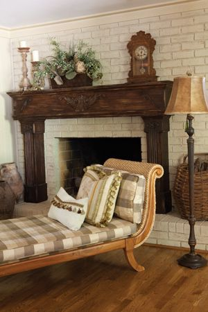 This darkly stained mantel stands out against the painted brick of the wall and hearth