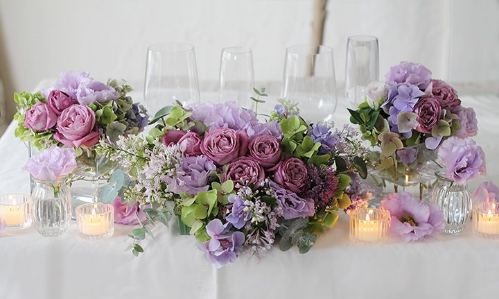 紫のバラやライラックを使ったメインテーブル装花。 紫はきつい色というイメージもありますが、淡い色でまとめているため上品で洗練された会場装花になりました。