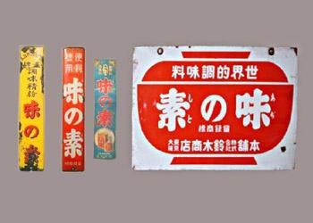 「お椀マーク」の看板は昭和10年頃の最初の軒吊りホーロー看板です。「お椀マーク」は明治42年の商標登録以来、現在でも使われているお馴染みのものです。お椀型のほか短冊型柱掛け、横書き、五色看板、矢入り吊り看板など多種類ありました。中でも好評だったのは短冊型町名番地入りの看板だったということです。味の素は大正11年に、特約店から小売店まで全国すべての取扱店に「味の素」の看板を掲げるとの方針を立て、サイドカーに乗って全国くまなく巡回して看板を設置して回ったということです。この看板は昭和期のものです。