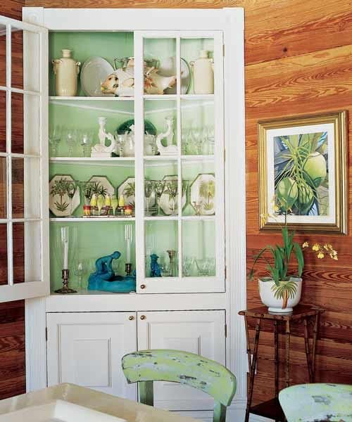 The minty hue of Pratt & Lambert's Grasshopper paint inside this corner cupboard creates a bright focal point in a pine-paneled dining room. | Photo: Tria Giovan