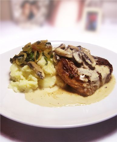 A succulent Rib Eye Steak with a creamy mushroom sauce, mashed potatoes and greens