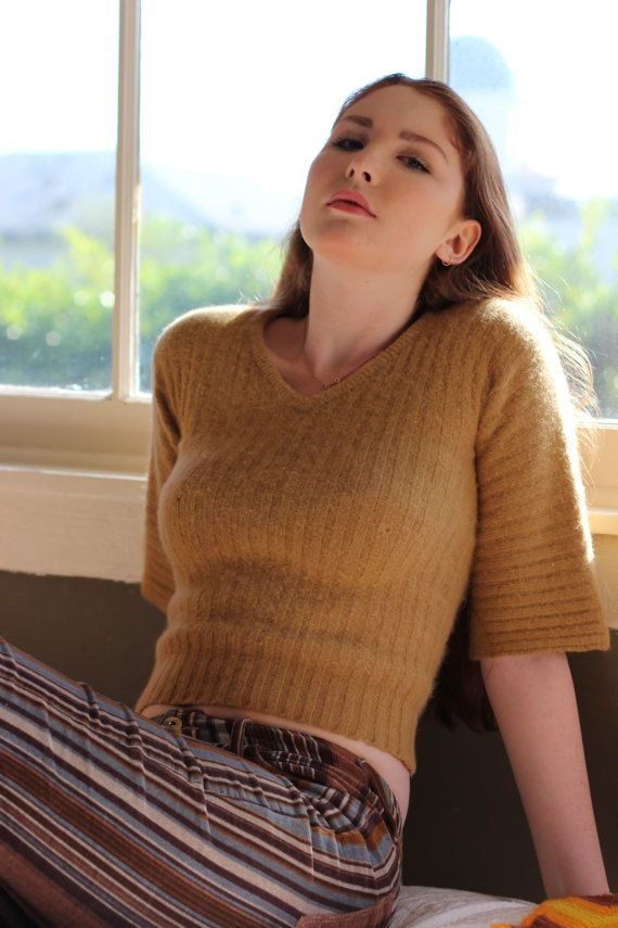 This vintage 70s sweater top is just right for fall. Made of wool and angora, its perfect to keep you warm and cozy all season long. I think our favorite part, though, has to be those righteous throwback sleeves!  Made of 56% lambswool / 40% angora rabbit hair / 4% nylon Super cozy Throwback bell sleeves Mustard yellow High v-neck  Fits like an XSMALL to SMALL Bust: 29 (not stretched), 41 (stretched) Sleeve length: 11.5 Sleeve width: 13 Garment length: 19  All measurements taken lying flat…