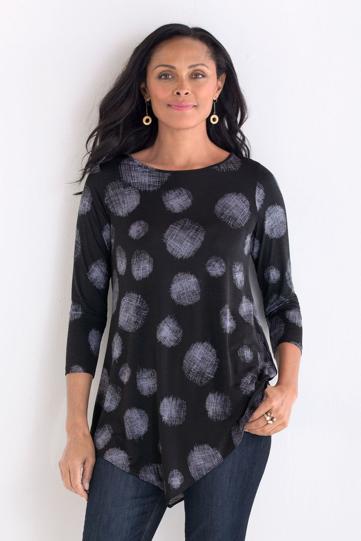 Galina Dot Tunic by Comfy USA. With a bold graphic print of cross-hatched dots, this tunic is utterly captivating, from the jewel neckline to its asymmetrical hem points. In a fluid knit with a soft, silky feel.