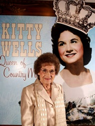 """Country Music Hall of Fame and Museum shows music pioneer Kitty Wells at an exhibit honoring her career in Nashville, Tenn. Wells, the first female superstar of country music, has died at the age of 92. The singer's family says Wells died at her home Monday after complications from a stroke. Her recording of """"It Wasn't God Who Made Honky Tonk Angels"""" in 1952 was the first No. 1 hit by a woman soloist on the country music charts."""