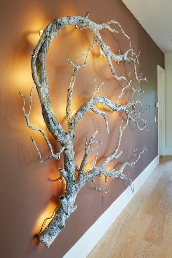 parede decorada com galho seco de arvore iluminado