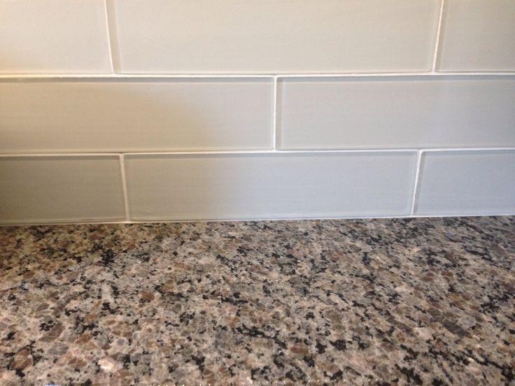 New Caledonia Granite Countertops And White Glass Tile Backsplash