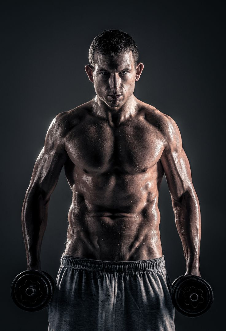 Muscular male fitness trainer portrait - Muscular male posing with weights