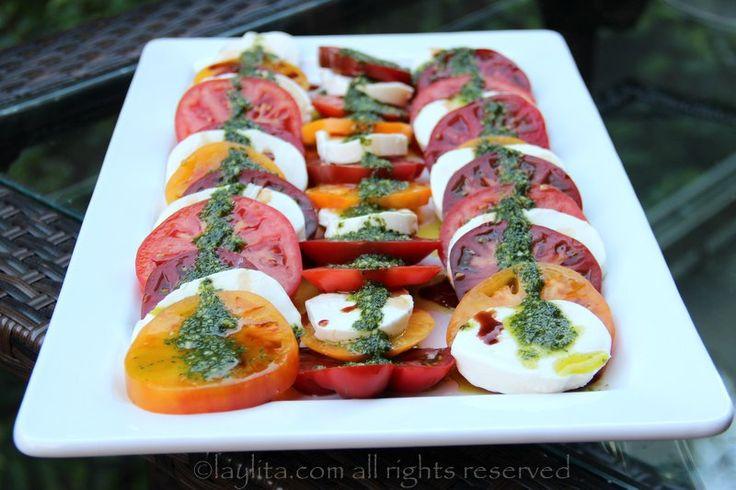 Receta fácil para preparar una deliciosa ensalada caprese de tomate y mozzarella con reducción balsámica y aceite de albahaca.