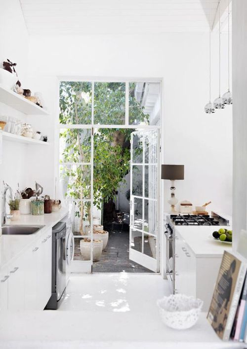 Clean white cabinets, Wall shelving, Pendant lights, Open to outdoors, White floor #mykitchenvision
