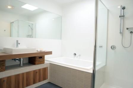 FITZROY BATHROOM Designed by Russell Henderson Built by SmarterBathrooms  Laminex Sublime Teak, Tiled hob, exposed plumbing