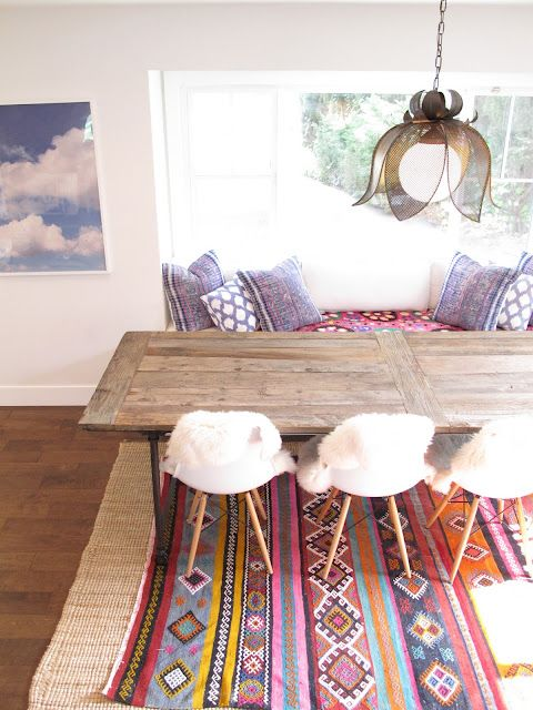 Eclectic dining room. Colorful rug. Rustic table. Mid century chairs with sheepskin covers. Color bench seating.