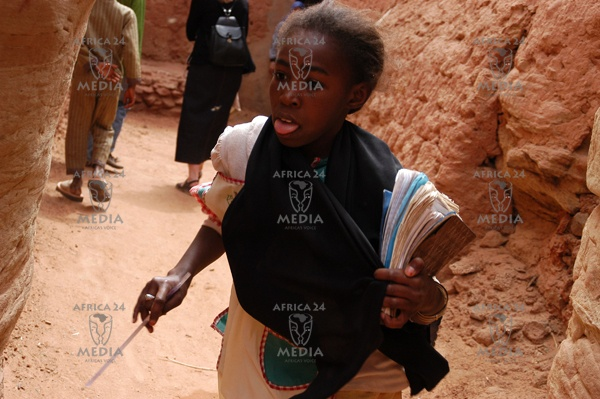 In the small village near Adrar a young girl is running home from school in the narrow streets of Tamentit, dug in red rock.