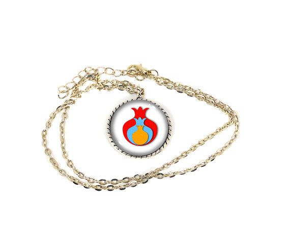 This Armenian pomegranate necklace measures 1 (2.5cm) in diameter.  It has a glass dome cover and the image inside features the shape of a pomegranate with the colors of the Armenian flag. The pendant setting is made of antique silver alloy, whereas the curb chain is made of alloy as well.   This necklace has a lobster clasp, extender on the ends, and measures 20 (51cm) in length.  For more of our Armenian items please visit this section in our shop…