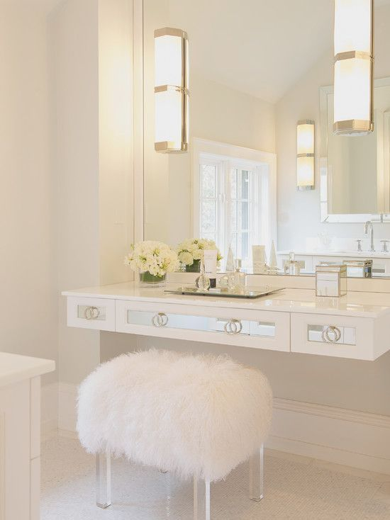 Beautiful bathroom with white mirrored floating vanity accented with white sheepskin vanity stool with lucite base paired with polished nickel sconces on white lacquered mirror. #makeupvanity