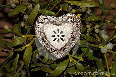 Gold heart on a background of mistletoe