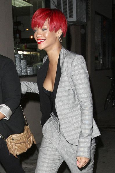 Rihanna Photos Photos - Red-headed Rihanna leaves her hotel and heads to Emilio's Ballato restaurant in Manhattan. Later in the day, Rihanna returned to the East Side Ink Tattoo salon where she reportedly had an inscription tattooed on the left side of her neck which her current beau, Matt Kemp, had helped her chose.  Rihanna was carrying a Vlieger & Vandam bag with a hand gun shape emblazoned on the base of the bag. - Rihanna at Emilio's Ballato