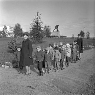 HK19880108:14863 lapsia ja opettajia Jätkänpuistossa Rovaniemellä, taustalla Kemijoki Oy:n lahjoittama Jätkä-patsas